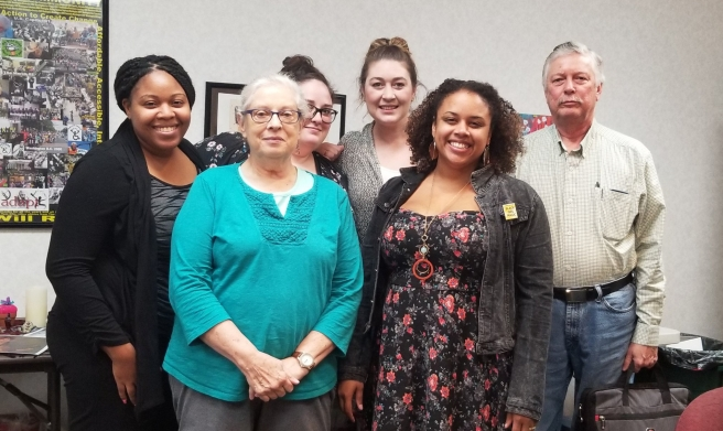 A group of 6 people that are intergenerational and racially diverse. There are 4 people in the back of the group. From left to right, a black woman smiles and is wearing a black sweater and grey patterned shirt, one white women wearing glasses and her dark brown hair in a bun smiles, another white woman smiles with her brown hair up in a bun, and a white older man in a button down shirt and jeans. In the front is an older woman with white hair and glasses. She's wearing a turquoise shirt and glasses. A brown skinned woman wears a flowered sun dress, jean jacket and gold jewelry with curly hair smiles.