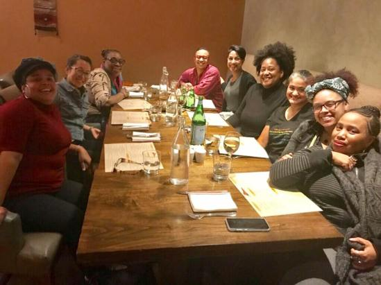 9 people of color share a table. They're all smiling at the camera and the table is full of glasses and menus.