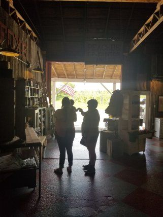 A person is holding a baby who is reaching out to another person who is touching the baby's hand. They are silhouettes in the open doorway of a barn marketplace. There are various shelves around them.