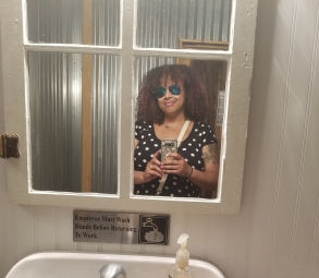 A brown woman stands in a bathroom mirror shaped like a window and snaps a selfie. She is wearing reflective sunglasses and a blue dress with white polka dots.